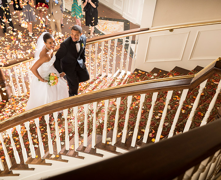 A bride and groom walk together up a grand staircase with confetti flying around and on the floor behind them