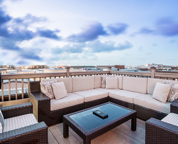 rooftop bar seating with brown wicker furniture against a blue cloudy sky