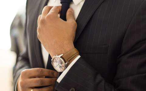 man wearing a dress watch adjusting his tie