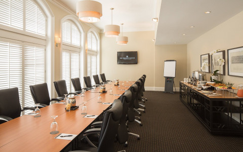 executive conference table with black chairs and buffet setup