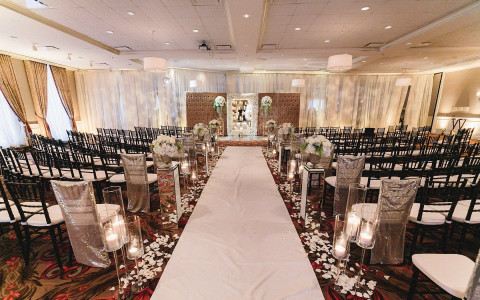 wedding ceremony seating with white flower petals and candles