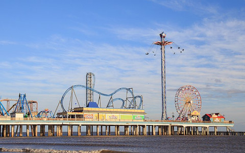 galveston pier amusement rides and ocean with blue sky