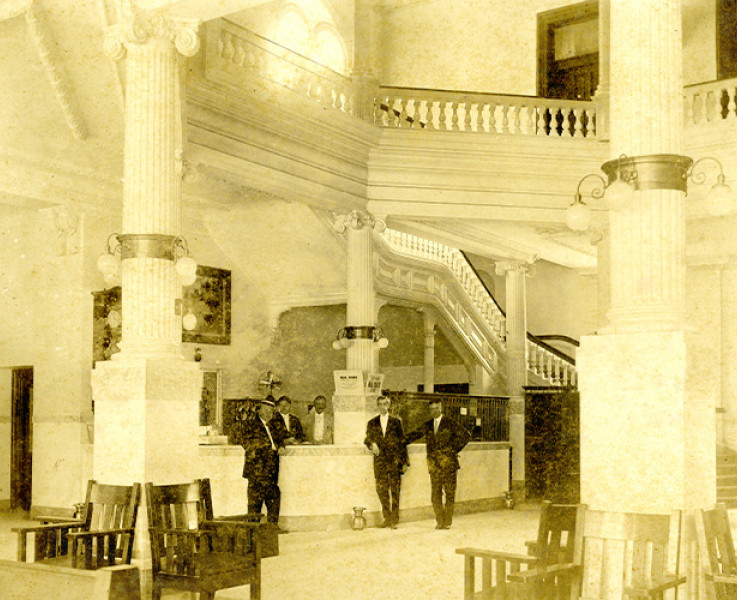 Black and white image with a yellow sepia tint of men standing around at a hotel check in area