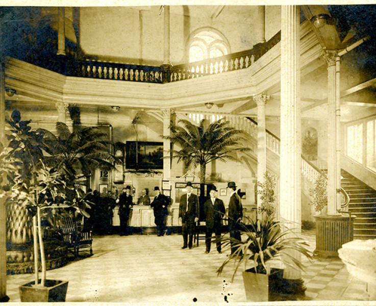Black and white image with a yellow sepia tint of a hotel reception area with small palm treed and a large staircase