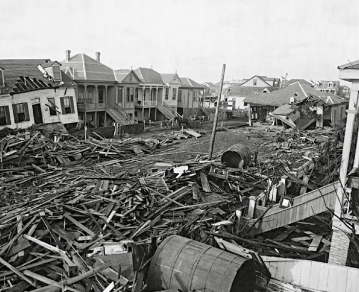 Black and white photo of piles of wood and debris in the center of a residential street destroyed by a hurricane