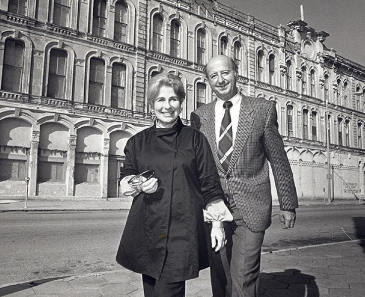Black and white photo of a man and a woman walking together on a street in front of a large building
