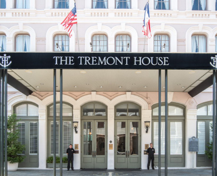 Close up of the tremont hotel entrance with a black covered area, light tan building with white trim, and light green doors