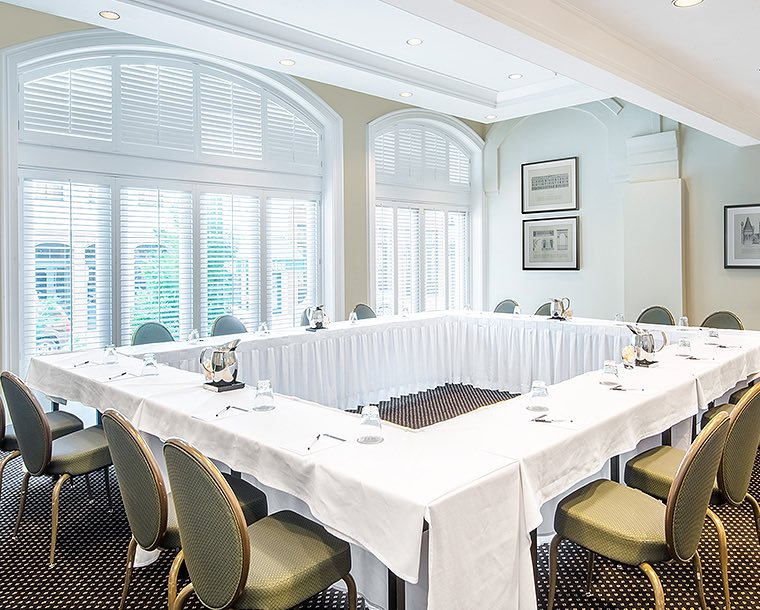 white tables arranged in a square for meeting in Ann M Gray room