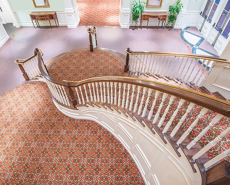looking down a grand wooden staircase with red carpet