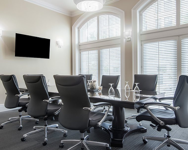 black executive conference table with black chairs in Colonel Moody room