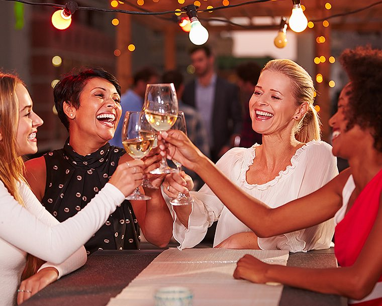 group of women toasting wine glasses under outdoor lights