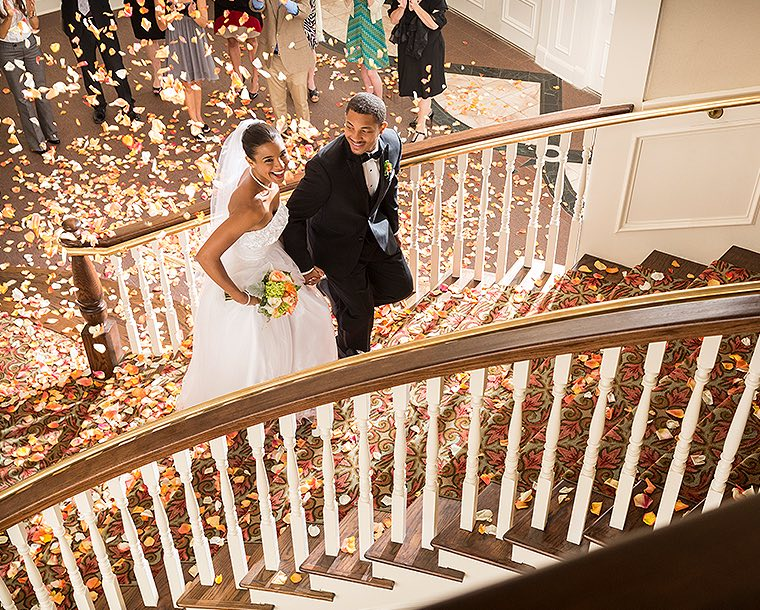 newly wed young couple laughing and walking up red carpet stairs