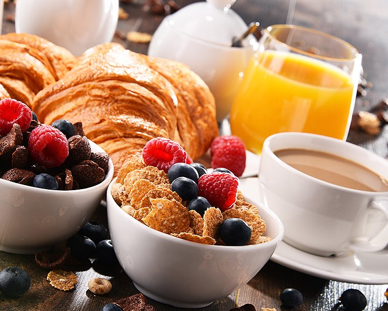 A table full of breakfast foods that includes, bowls of cereal topped with fresh blueberries and raspberries, coffee, croissants, and a glass or orange juice