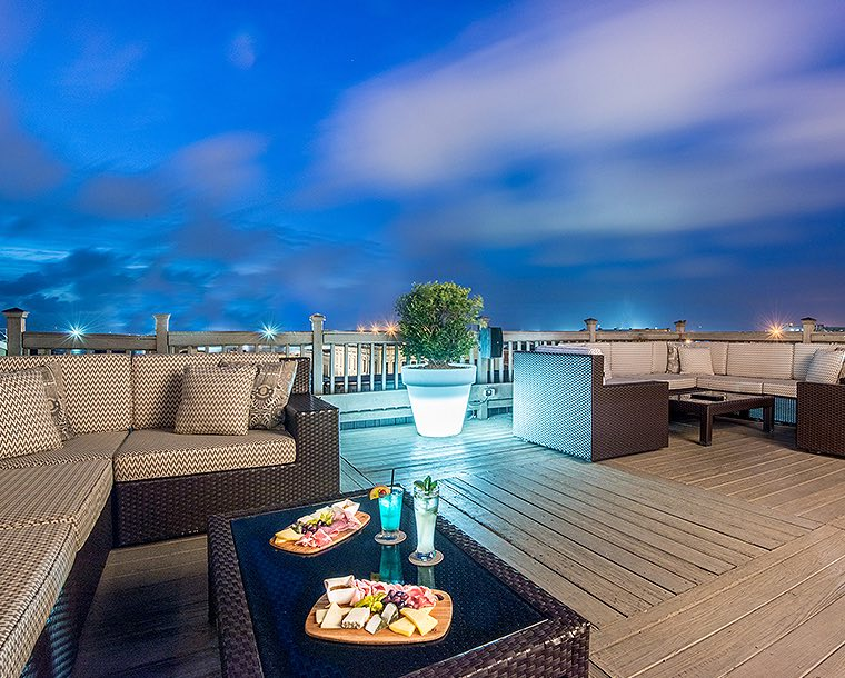 rooftop bar at night with seating and meat and cheese boards