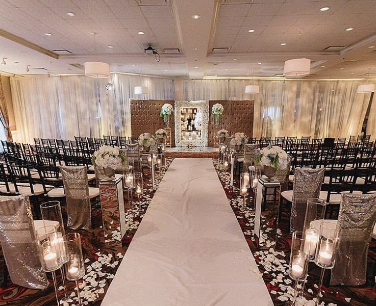 wedding ceremony seating with black chairs and high ceilings