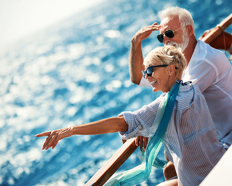 couple on a cruise ship smiling and pointing out to a blue sea