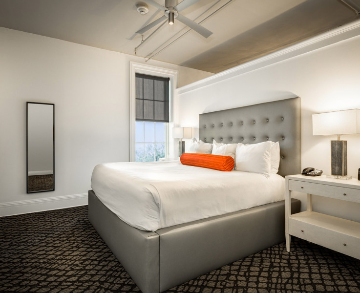 white queen bed with grey tufted headboard in a room with white walls