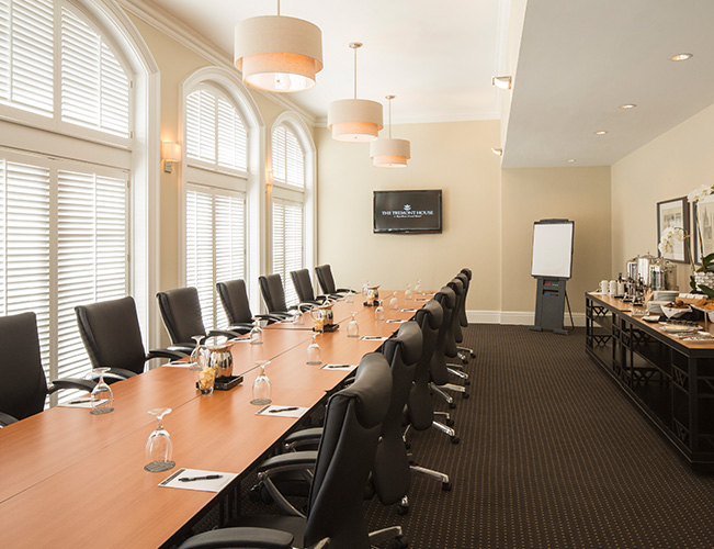 long wooden conference table with black leather chairs in a white room with bay windows