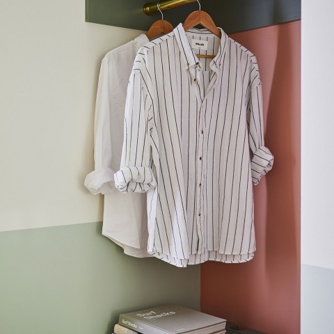 2 collard shirts hung in closet