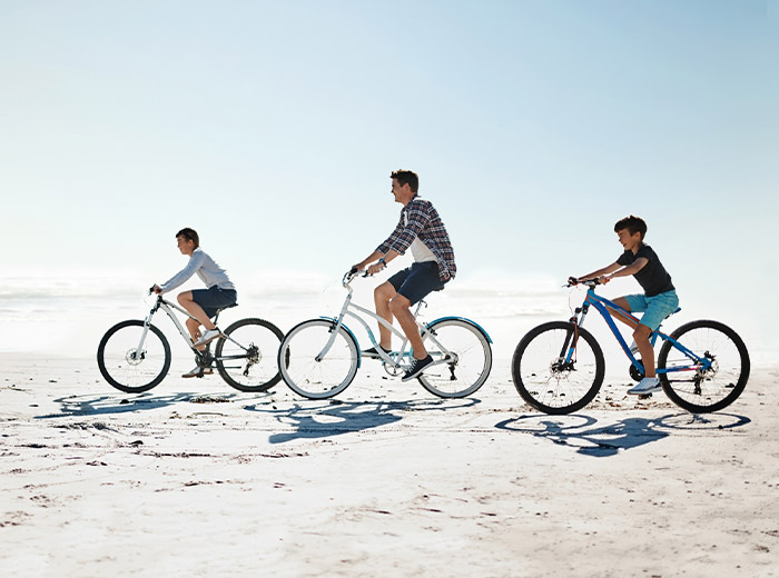 people riding bike on beach