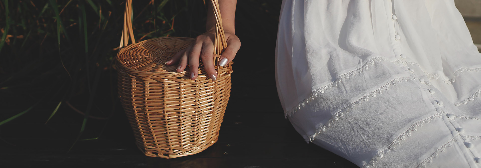 woman in white dress holding a wicker basket