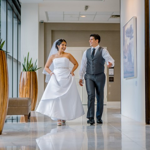 bride and groom walking through a hall way