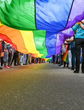 low shot of people standing below a pride flag on a paved road