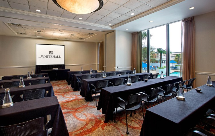 event space with 2 columns and 5 rows of tables with single projection screen at the head of the room