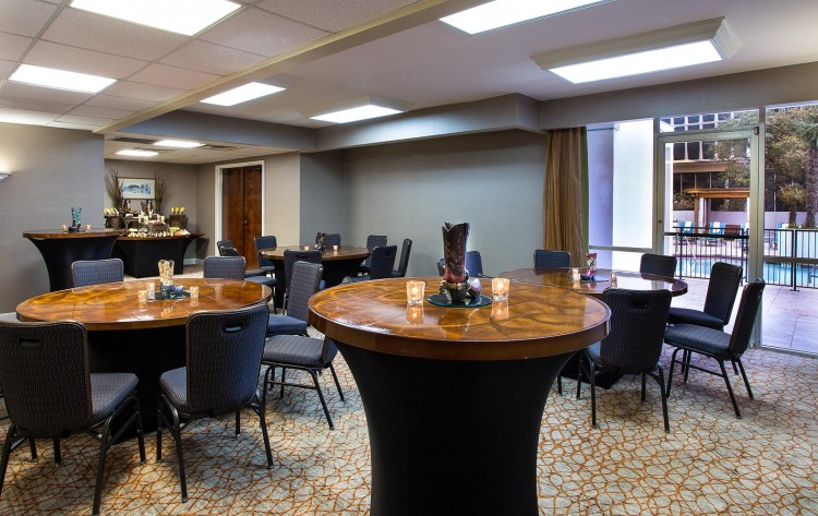 small event room off of pool with bar and several round tables and high tops