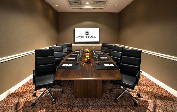 boardroom with large conference table, leather chairs, and tv
