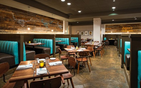interior dining for hotel restaurant Edgars Hermanos is made of tables and booths. Accents of unfinished wood and teal blue