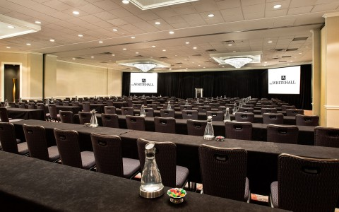 Event room set up for a conference with several long rows of tables with black table clothes facing 2 projection screens and podiums