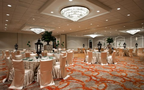 formal event room with chandeliers and multiple circular tables dressed in formal table wear