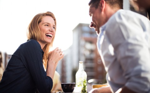 women laughing with man over coffee