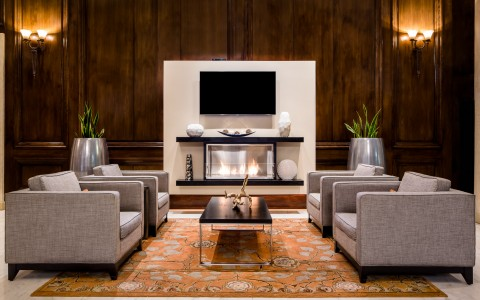 hotel lobby seating area features a large wood accent wall with fire place and mounted tv. 4 large lounge chairs former seating area