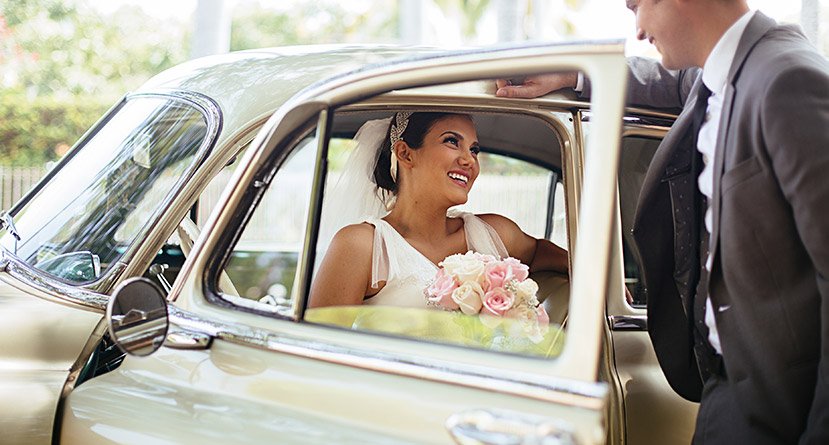 husband greeting his wife at door of classic car