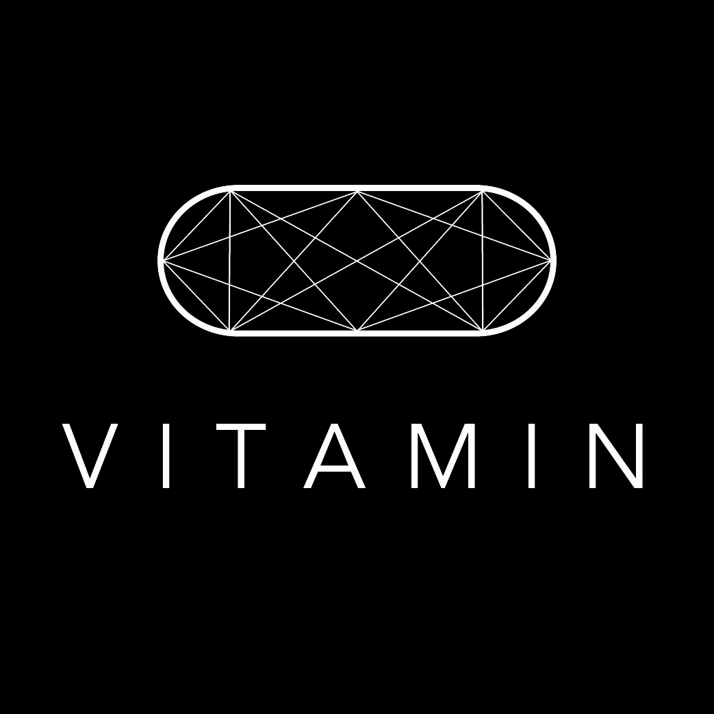 white geometric pill shape on a black background with the word vitamin