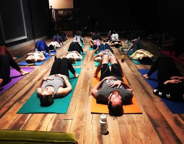 people in a yoga studio laying on colorful mats on a natural wood floor