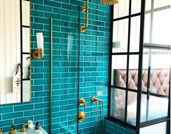 glass shower with gold fixtures and teal subway tile