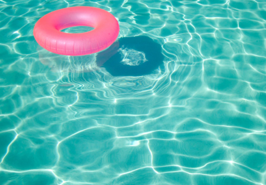 pink inner tube floating in turquoise pool