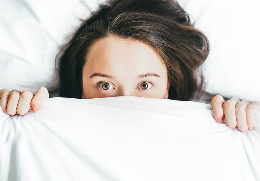 woman peeking out of bed