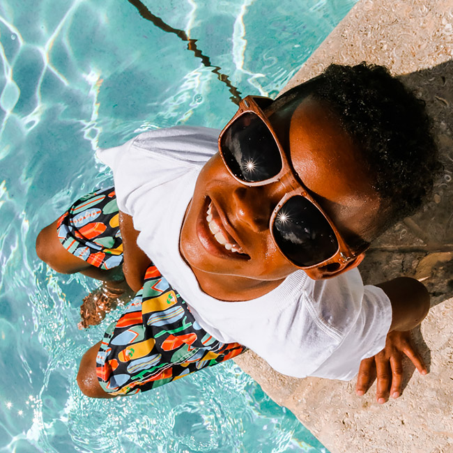 kid with sunglasses relaxing by the pool
