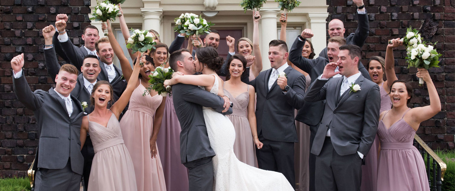 bride and groom kissing while bridal party cheers them on