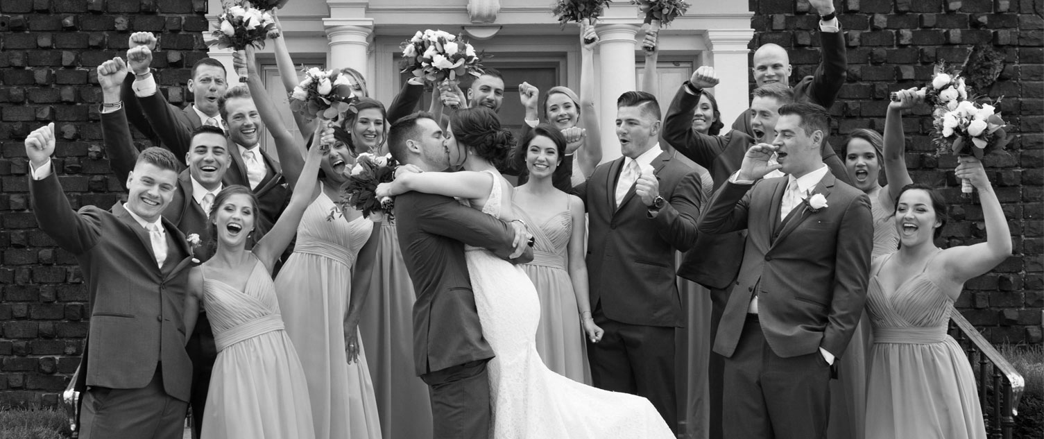 bride and groom kissing while bridal party cheers them on BW