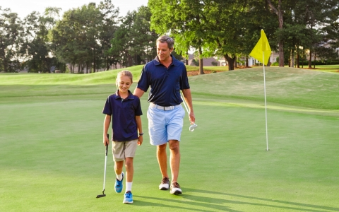 father and son walking through a golf course