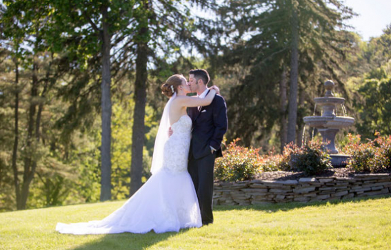 bride and groom kissing on lawn in front of fountain