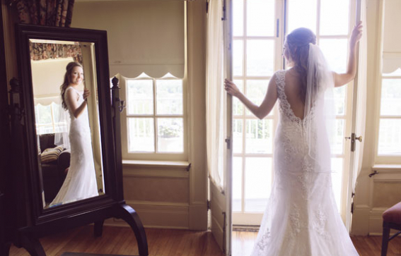 bridge in gown posing amoung open french doors while looking at reflection in the mirror