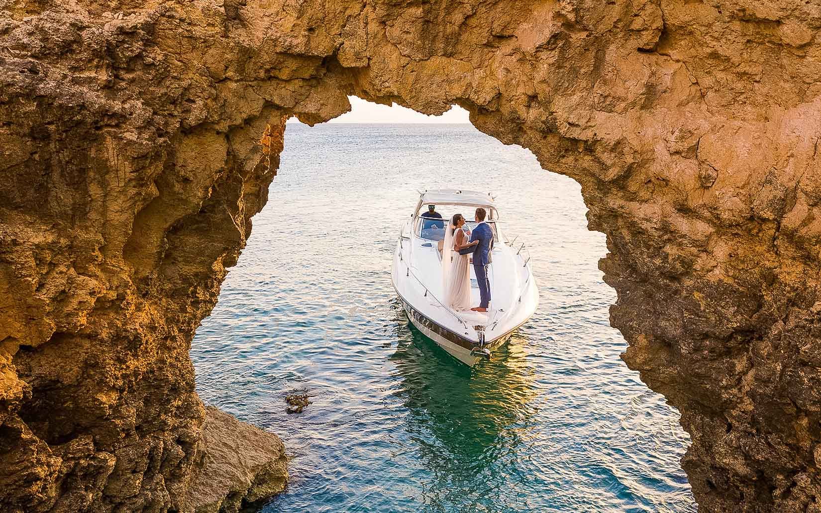 bride and groom on boat as it enters cave opening