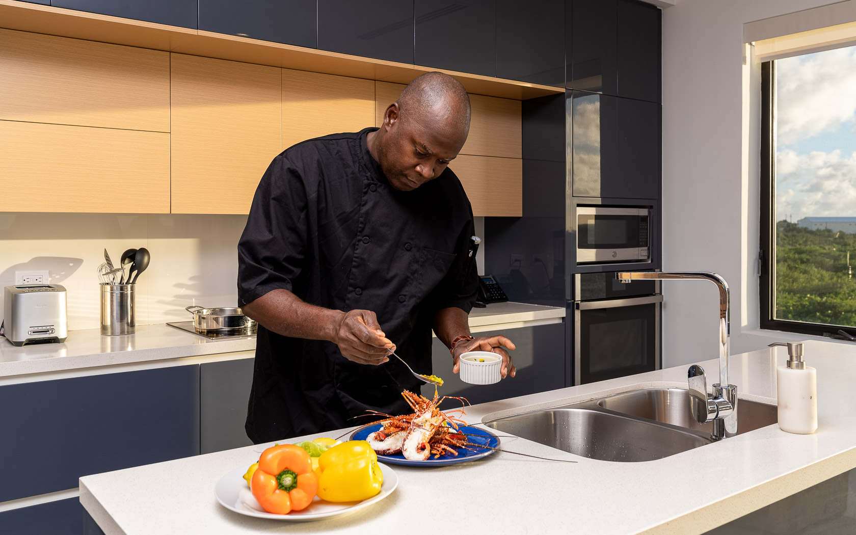 chef plating lobster meal in spacious kitchen