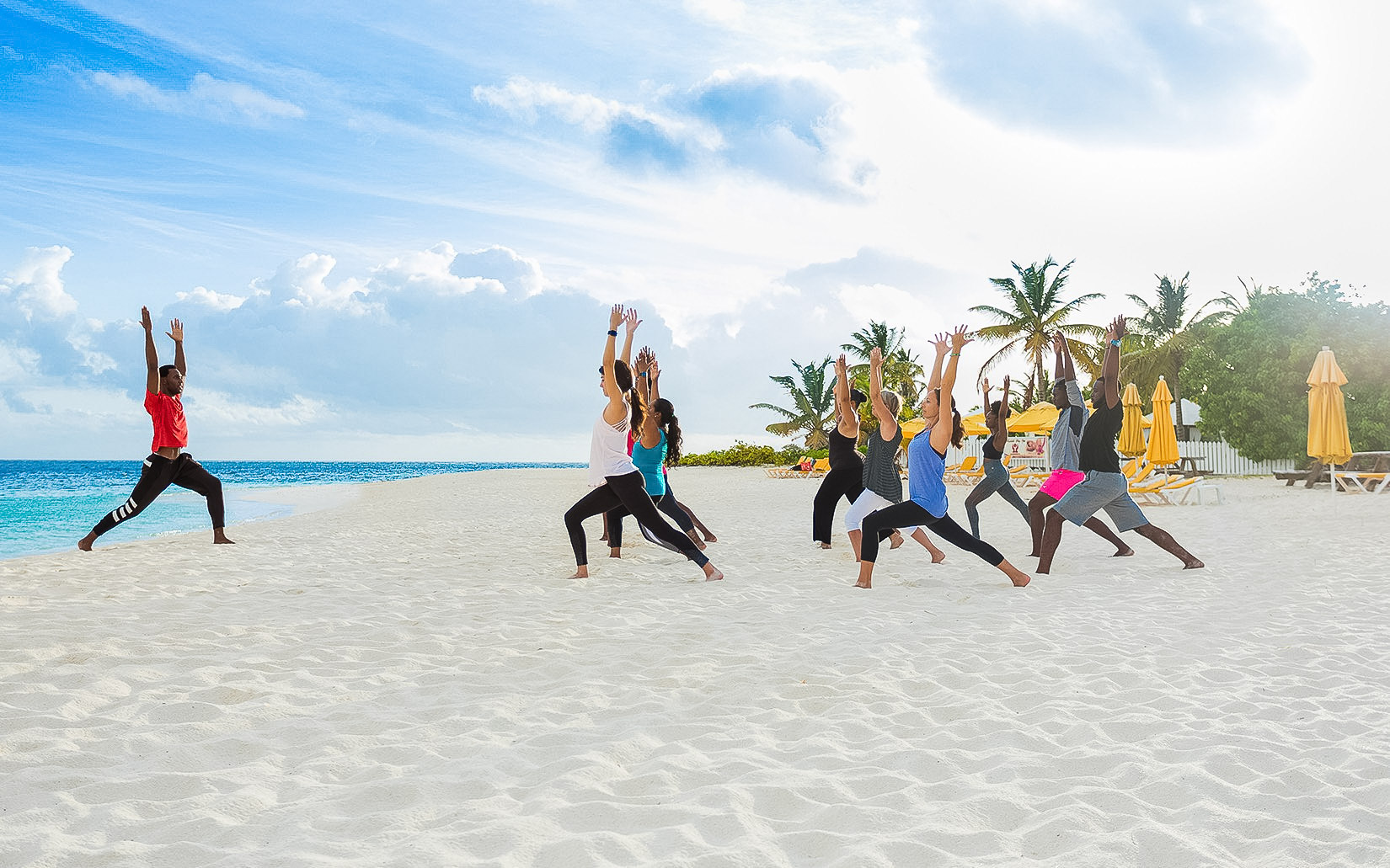 instructor leading group yoga class on beach